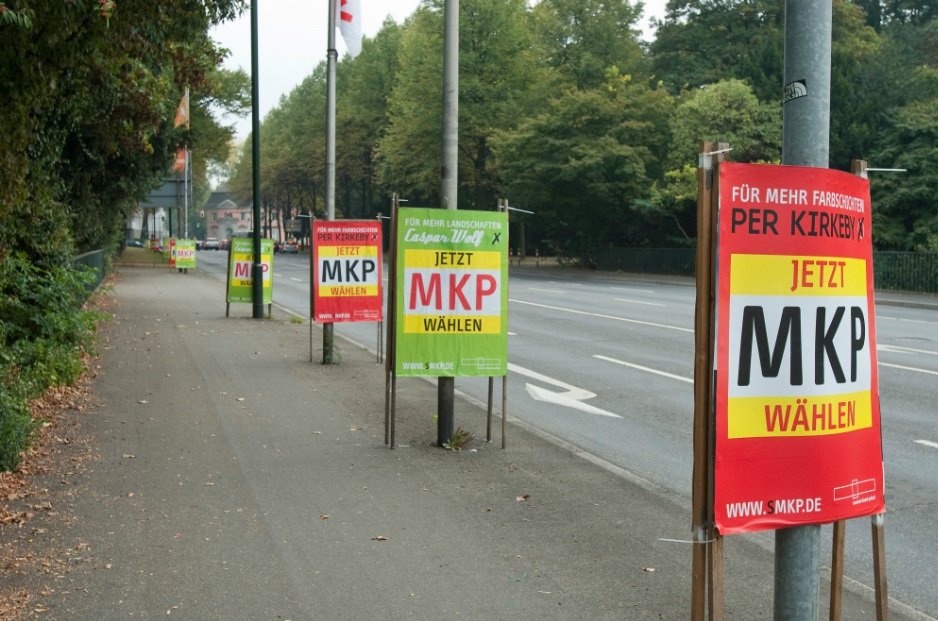 Pasting our posters over election posters: Vote MKP!